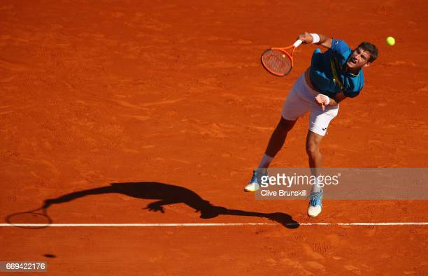 Pablo Carreno Busta of Spain serves against Fabio Fognini of Italy in their first round match on day two of the Monte Carlo Rolex Masters at...