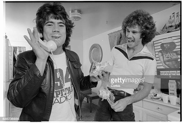 Pablo Cruise keyboardist Cory Lerios tries to talk on the phone and eat a sandwich at the same time Fellow musician Dave Jenkins looks on with...