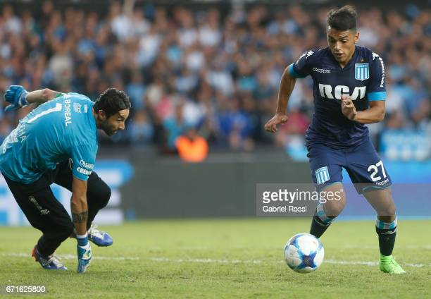 Pablo Cuadra of Racing Club drives the ball as Cristian Lucchetti of Atletico de Tucuman tries to catch it during a match between Racing and Atletico...