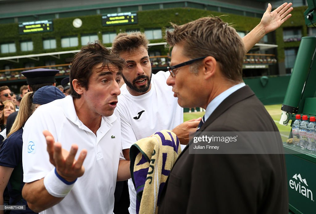Pablo Cuevas of Uraguay and Marcel Granollers of Spain argue with the match referee during the Men's Doubles third round match against Jonathan...
