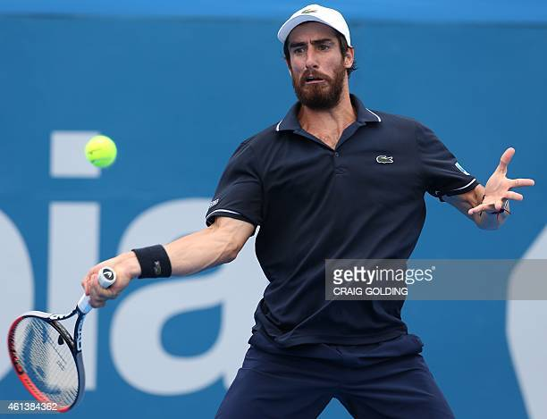 Pablo Cuevas of Uruguay hits a return against Nicolas Almagro of Spain during their men's singles match on day two of the Sydney International tennis...