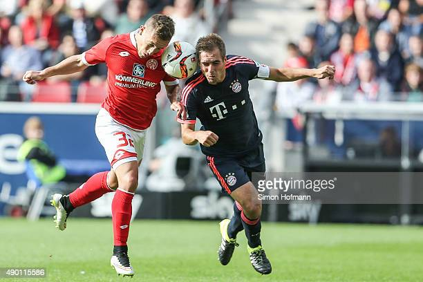 Pablo de Blasis of Mainz is challenged by Philipp Lahm of Muenchen during the Bundesliga match between 1 FSV Mainz 05 and FC Bayern Muenchen at...