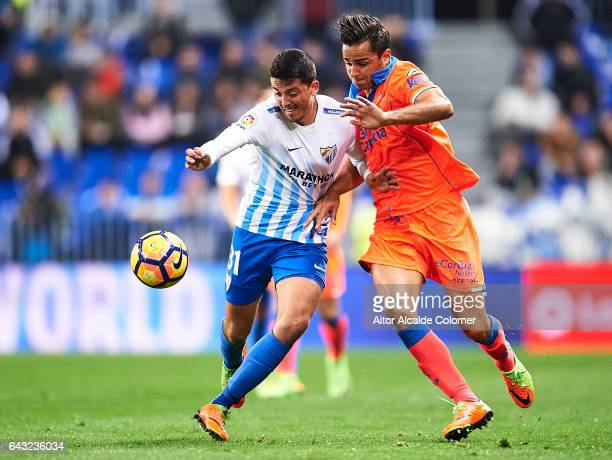 Pablo Fornals of Malaga CF competes for the ball with David Simon of Union Deportiva Las Palmas during La Liga match between Malaga CF and UD Las...