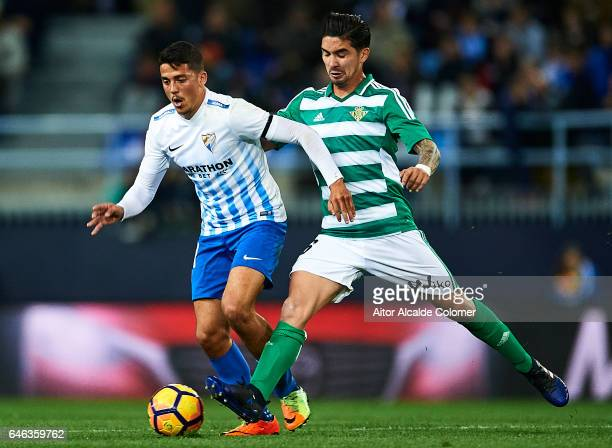 Pablo Fornals of Malaga CF competes for the ball with Felipe Gutierrez of Real Betis Balompie during La Liga match between Malaga CF and Real Betis...