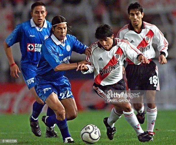 Pablo Galdames of the team Cruz Azul de Mexico vies for control of the ball against Damian Alvarez of River Plate as Victor Gutierrez and Nelson...