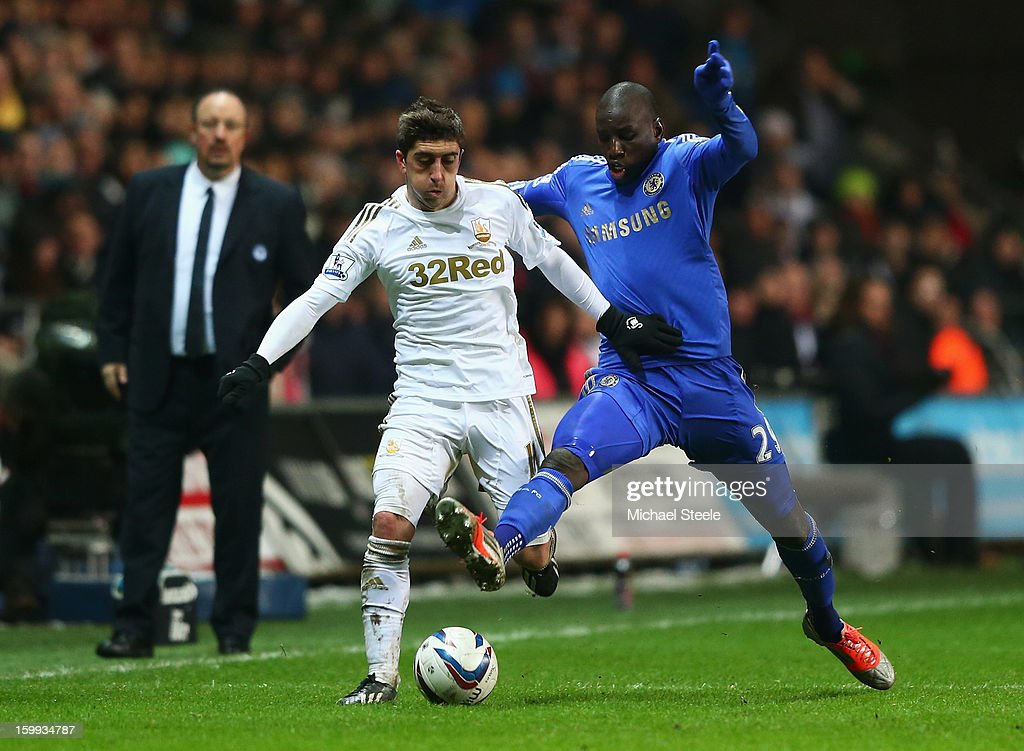 Pablo Hernandez of Swansea City is challenged by <a gi-track='captionPersonalityLinkClicked' href=/galleries/search?phrase=Demba+Ba&family=editorial&specificpeople=4510297 ng-click='$event.stopPropagation()'>Demba Ba</a> of Chelsea as Rafael Benitez interim manager of Chelsea looks on during the Capital One Cup Semi-Final Second Leg match between Swansea City and Chelsea at Liberty Stadium on January 23, 2013 in Swansea, Wales.