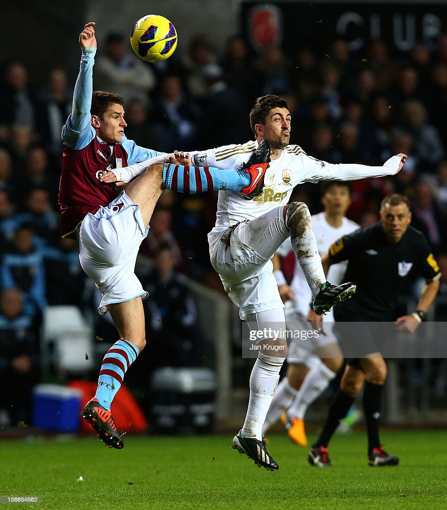 Pablo Hernandez of Swansea City is struck in the face by the boot of Chris Herd of Aston Villa as he clears the ball during the Barclays Premier League match between Swansea City and Aston Villa at the Liberty Stadium on January 1, 2013 in Swansea, Wales.