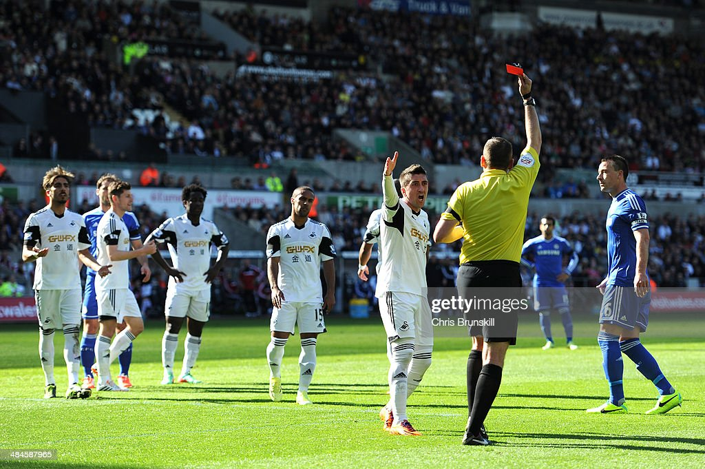 Pablo Hernandez of Swansea remonstrates with Referee Phil Dowd as he shows the red card to Chico Flores (L) of Swansea during the Barclays Premier League match between Swansea City and Chelsea at Liberty Stadium on April 13, 2014 in Swansea, Wales.