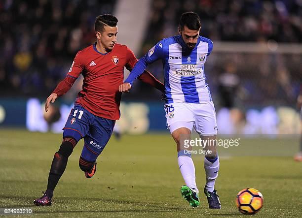 Pablo Insua of CD Leganes is held by Alex Berenguer of CA Osasuna during the La Liga match between CD Leganes and CA Osasuna at Estadio Municipal de...