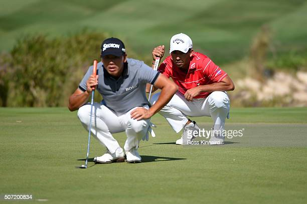 Pablo Larrazabal of Spain and Ashun Wu of China line up their putts on the 18th during the second round of the Commercial Bank Qatar Masters at the...