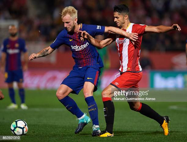 Pablo Maffeo of Girona competes for the ball with Ivan Rakitic of Barcelona during the La Liga match between Girona and Barcelona at Municipal de...