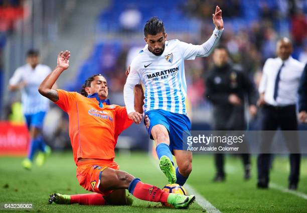 Pablo Mauricio Lemos of Union Deportiva Las Palmas competes for the ball with Michael Santos of Malaga CF during La Liga match between Malaga CF and...