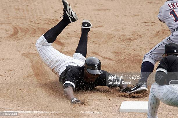 Pablo Ozuna of the Chicago White Sox safely slides into third base ahead of the tag by Brandon Inge of the Detroit Tigers in the 7th inning as third...