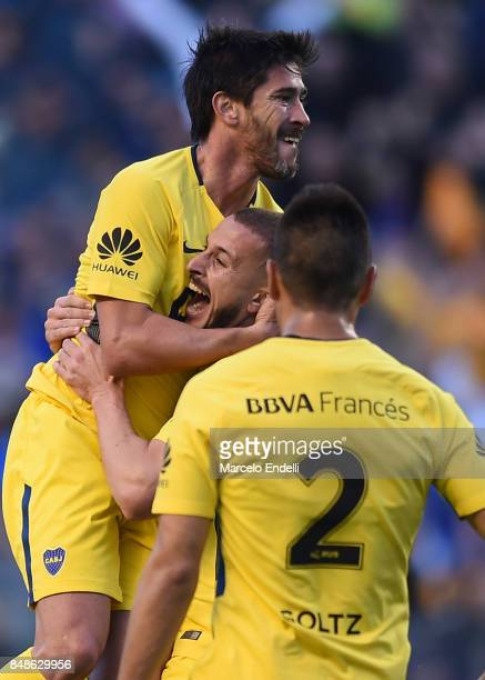 Pablo Perez of Boca Juniors celebrates with teammates Dario Bennedetto and Paolo Goltz after scoring the first goal of his team during a match...