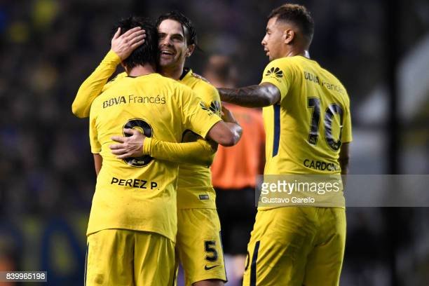 Pablo Perez of Boca Juniors celebrates with teammates Fernando Gago and Edwin Cardona after scoring the second goal of his team during a match...