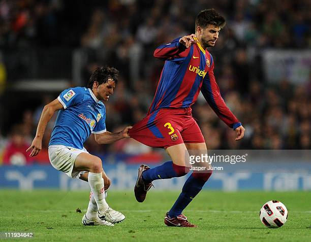 Pablo Piatti of Almeria tries to stop Gerard Pique of Barcelona by holding on to his football shorts during the la Liga match between FC Barcelona...