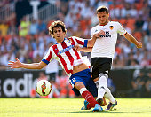 Pablo Piatti of Valencia is tackled by Tiago Cardoso of Atletico de Madrid during the La Liga match between Valencia CF and Club Atletico de Madrid...