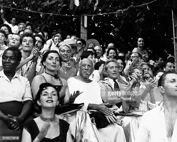 Pablo Picasso at a bullfight in Vallauris France together with his wife Jaqueline and Jean Cocteau and behind them with a scarf Picasso's daughter...