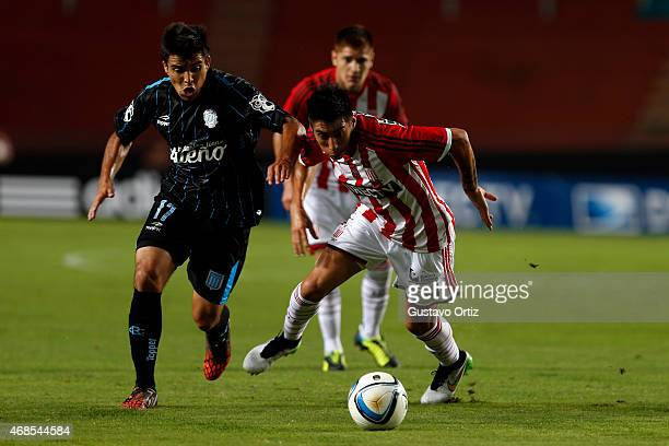 Pablo Rosales of Estudiantes drives the ball as he is followed by Marcos Acuña of Racing during a match between Estudiantes and Racing Club as part...