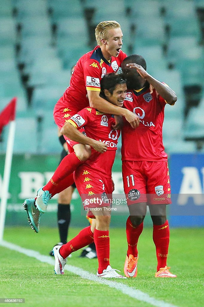 Pablo Sanchez of Adelaide celebrates with team mates James Jeggo and Bruce Djite after scoring a goal during the round 13 ALeague match between...