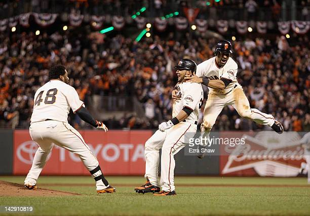 Pablo Sandoval and Angel Pagan celebrate with Melky Cabrera of the San Francisco Giants after Cabrera hit a fielders choice in the ninth inning to...