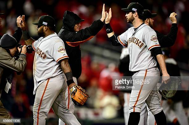 Pablo Sandoval and Brandon Belt of the San Francisco Giants celebrate with their teammates after defeating the Washington Nationals in the eighteenth...