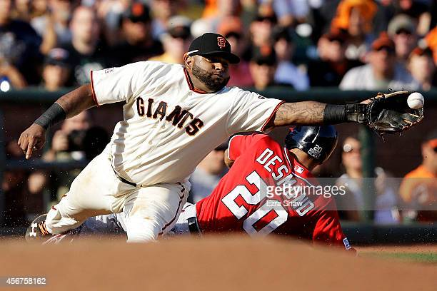 Pablo Sandoval fails to catch a throw by Madison Bumgarner of the San Francisco Giants on a bunt by Wilson Ramos of the Washington Nationals as Ian...