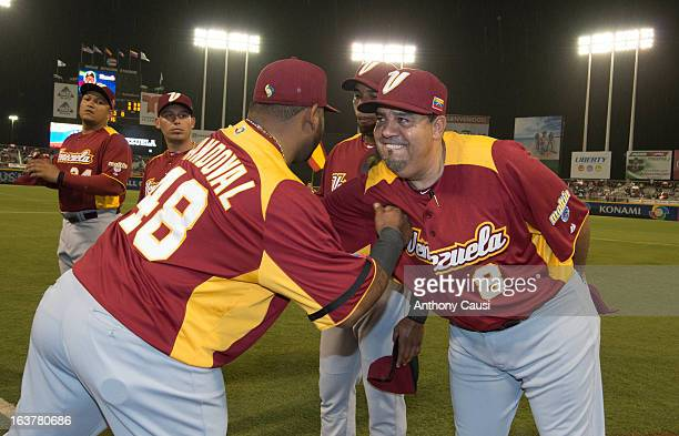 Pablo Sandoval of Team Venezuela is greeted by manager Luis Sojo of Team Venezuela during player introductions before Pool C Game 1 between Dominican...