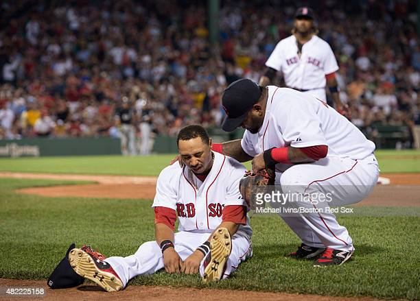 Pablo Sandoval of the Boston Red Sox checks on Mookie Betts after he fell over the outfield wall attempting to catch a home run hit by Jose Abreu of...