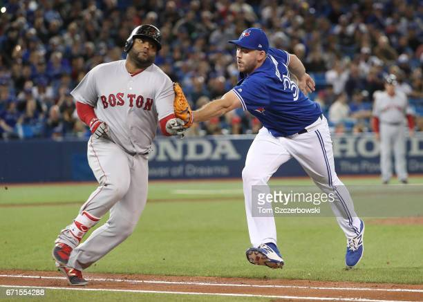 Pablo Sandoval of the Boston Red Sox is tagged out by Joe Biagini of the Toronto Blue Jays as he tries to run out a soft grounder in the seventh...