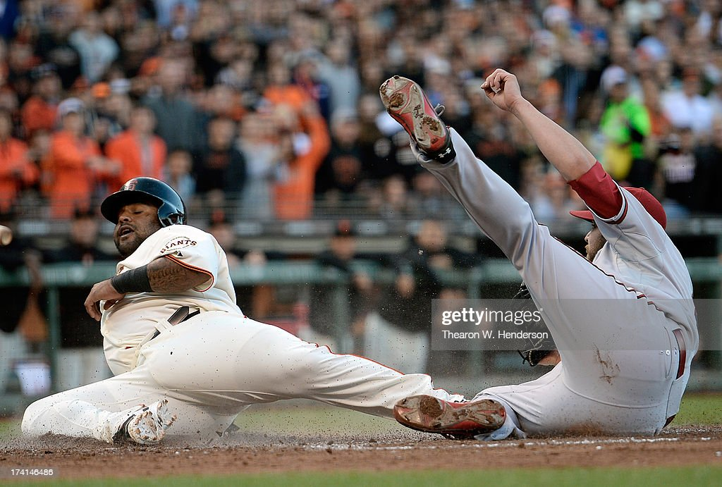 Pablo Sandoval #48 of the San Francisco Giants attempting to score on a wild pitch is tagged out by pitcher Wade Miley #36 of the Arizona Diamondback in the fourth inning at AT&T Park on July 20, 2013 in San Francisco, California.