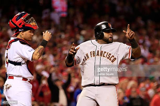 Pablo Sandoval of the San Francisco Giants celebrates scoring on a single by Hunter Pence in the sixth inning as Yadier Molina of the St Louis...