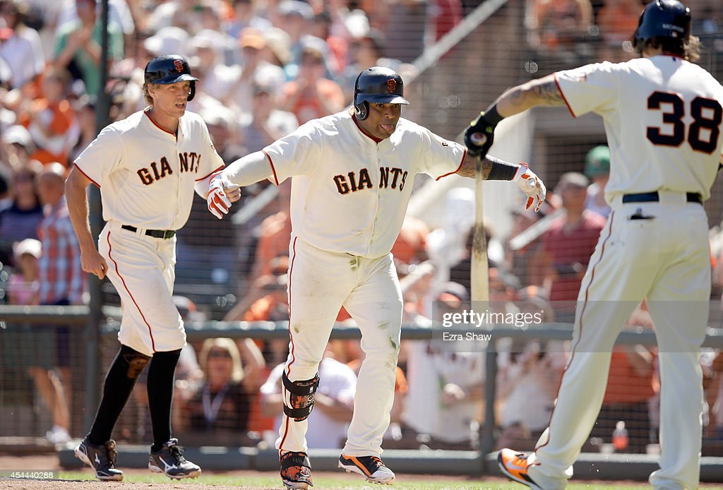 Pablo Sandoval #48 of the San Francisco Giants celebrates with Hunter Pence #8 and Michael Morse #38 after he hit a two-run home run in the fifth inning of their game against the Milwaukee Brewers at AT&T Park on August 31, 2014 in San Francisco, California.