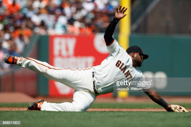 Pablo Sandoval of the San Francisco Giants dives for but is unable to field a ground ball hit for a single by Ben Lively of the Philadelphia Phillies...