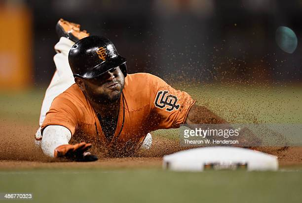 Pablo Sandoval of the San Francisco Giants dives into third base with a triple against the Cleveland Indians in the bottom of the seventh inning at...