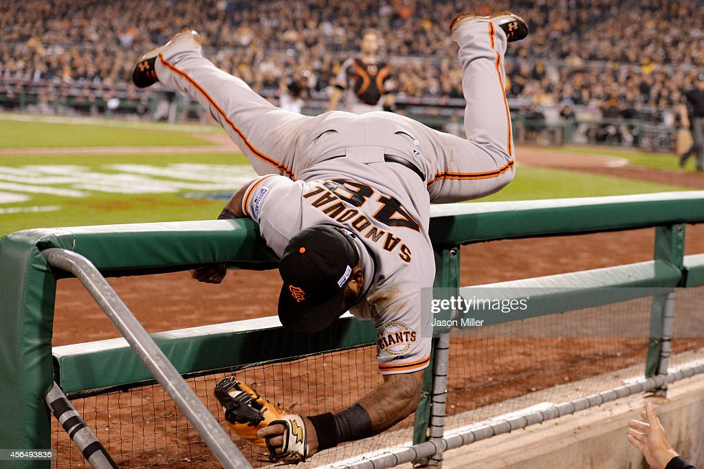 Pablo Sandoval #48 of the San Francisco Giants flips into the Pittsburgh Pirates dugout as he catches a fly ball hit by Russell Martin #55 of the Pittsburgh Pirates in the seventh inning during the National League Wild Card game at PNC Park on October 1, 2014 in Pittsburgh, Pennsylvania.