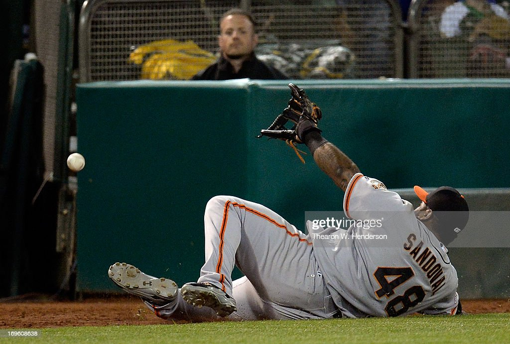 <a gi-track='captionPersonalityLinkClicked' href=/galleries/search?phrase=Pablo+Sandoval&family=editorial&specificpeople=803207 ng-click='$event.stopPropagation()'>Pablo Sandoval</a> #48 of the San Francisco Giants goes into a slide but is unable to make the catch on this foul ball off the Bat of Brandon Moss #37 of the Oakland Athletics in the seventh inning at O.co Coliseum on May 28, 2013 in Oakland, California.