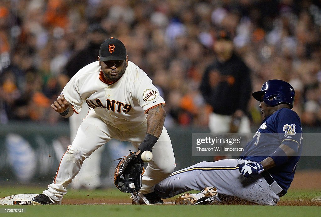 Pablo Sandoval of the San Francisco Giants has the ball thrown through his legs for an error allowing Yuniesky Betancourt of the Milwaukee Brewers to...