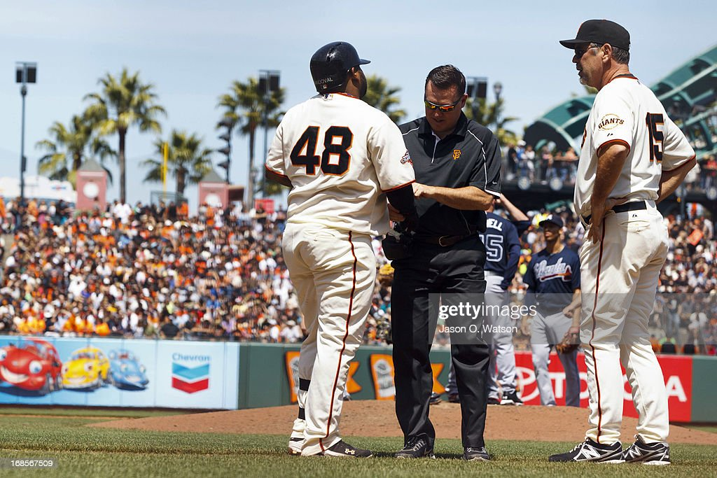 <a gi-track='captionPersonalityLinkClicked' href=/galleries/search?phrase=Pablo+Sandoval&family=editorial&specificpeople=803207 ng-click='$event.stopPropagation()'>Pablo Sandoval</a> #48 of the San Francisco Giants is attended to by trainer Dave Groeschner (C) and manager <a gi-track='captionPersonalityLinkClicked' href=/galleries/search?phrase=Bruce+Bochy&family=editorial&specificpeople=220291 ng-click='$event.stopPropagation()'>Bruce Bochy</a> #15 after getting hit by a pitch by the Atlanta Braves during the fifth inning at AT&T Park on May 11, 2013 in San Francisco, California.
