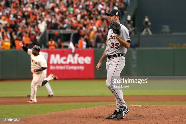 Pablo Sandoval of the San Francisco Giants rounds the bases after hitting a solo home run to center field as Justin Verlander of the Detroit Tigers...