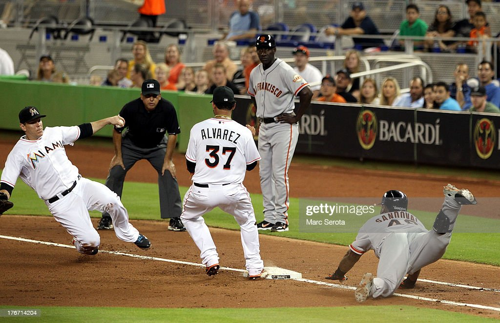<a gi-track='captionPersonalityLinkClicked' href=/galleries/search?phrase=Pablo+Sandoval&family=editorial&specificpeople=803207 ng-click='$event.stopPropagation()'>Pablo Sandoval</a> #48 (R) of the San Francisco Giants slides into first base against the Miami Marlins during the fourth inning at Marlins Park on August 17, 2013 in Miami, Florida.