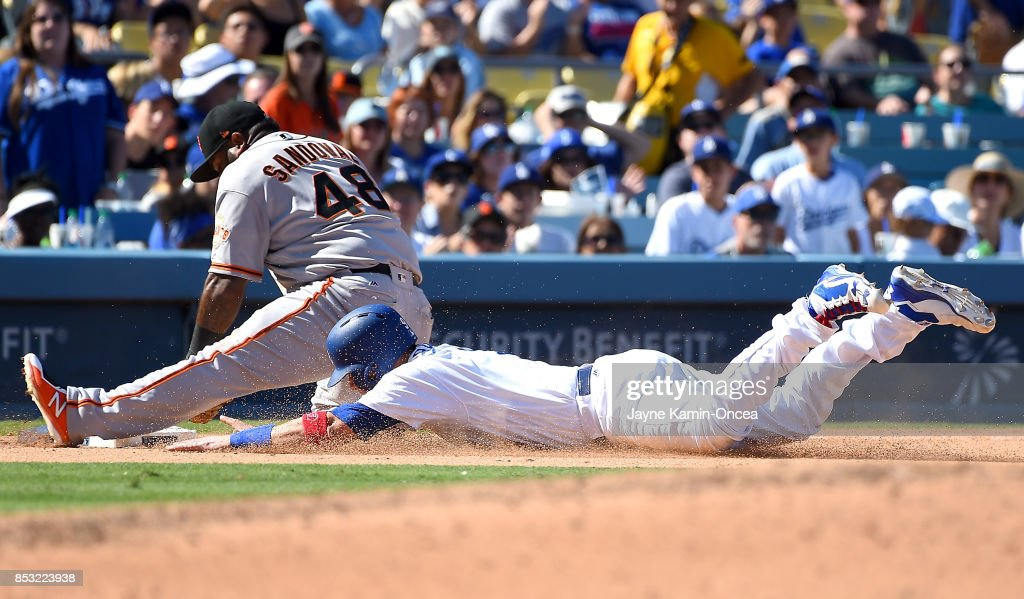 Pablo Sandoval #48 of the San Francisco Giants tags out a diving Yasmani Grandal #9 of the Los Angeles Dodgers at third base in the sixth inning of the game at Dodger Stadium on September 24, 2017 in Los Angeles, California.