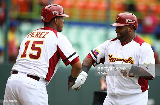 Pablo Sandoval of Venezuela celebrates his home run with Salvador Perez after hitting a home run against Spain during the first round of the World...