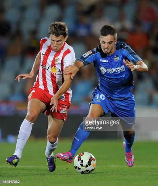 Pablo Sarabia of Getafe CF holds back Sebastian Dubarbier of UD Almeria holds off battles for the ball against during the La Liga match between...