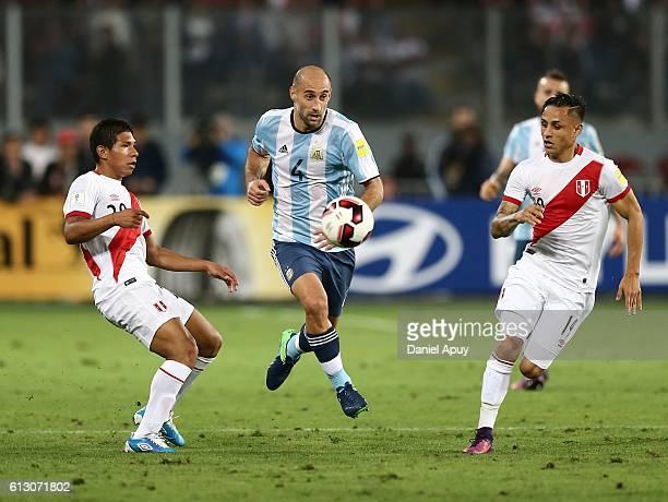 Pablo Zabaleta of Argentina tries to pass between Yoshimar Yotun and Edison Flores of Peru during a match between Peru and Argentina as part of FIFA...