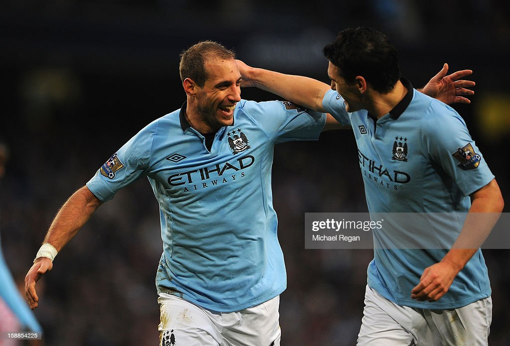 Pablo Zabaleta of Manchester City celebrates scoring the opening goal with team-mate Gareth Barry (R) during the Barclays Premier League match between Manchester City and Stoke City at the Etihad Stadium on January 1, 2013 in Manchester, England.