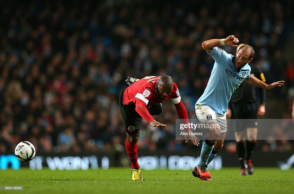 Pablo Zabaleta of Manchester City fouls <a gi-track='captionPersonalityLinkClicked' href=/galleries/search?phrase=Jason+Scotland&family=editorial&specificpeople=583351 ng-click='$event.stopPropagation()'>Jason Scotland</a> of Barnsley during the FA Cup sponsored by Budweiser sixth round match between Manchester City and Barnsley at Etihad Stadium on March 9, 2013 in Manchester, England.