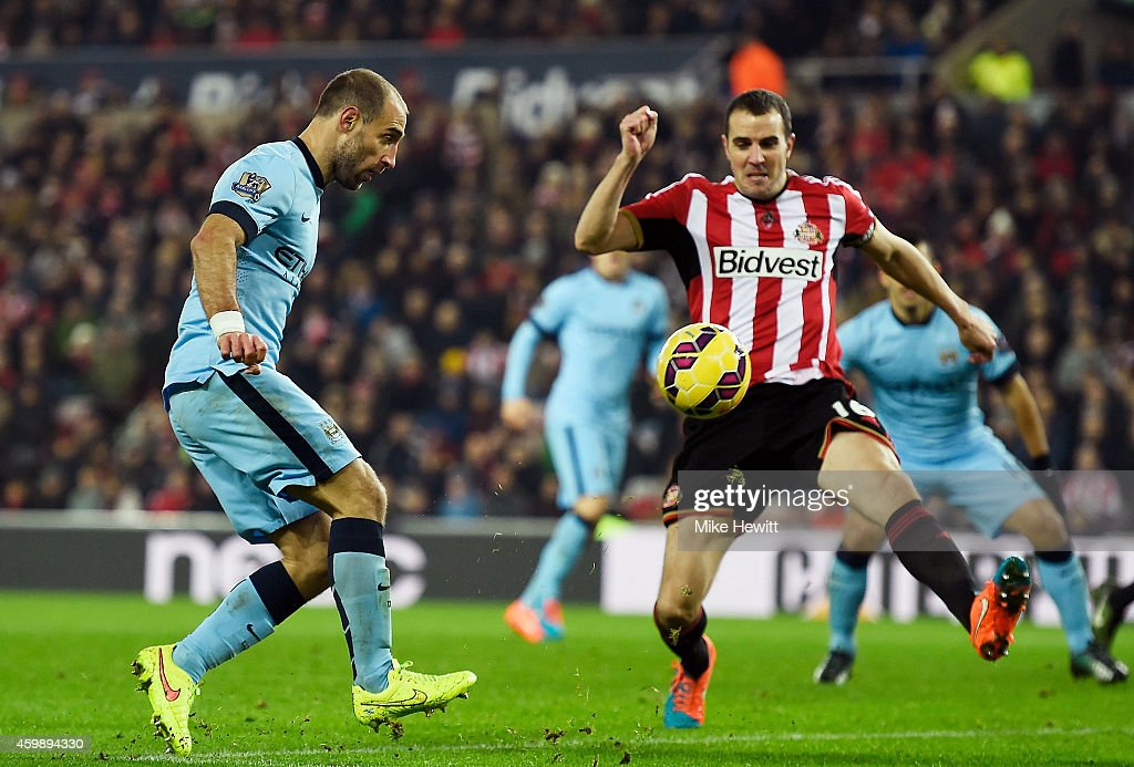 Pablo Zabaleta of Manchester City scores his team's third goal as John O'Shea of Sunderland closses in during the Barclays Premier League match between Sunderland and Manchester City at The Stadium of Light on December 3, 2014 in Sunderland, England.