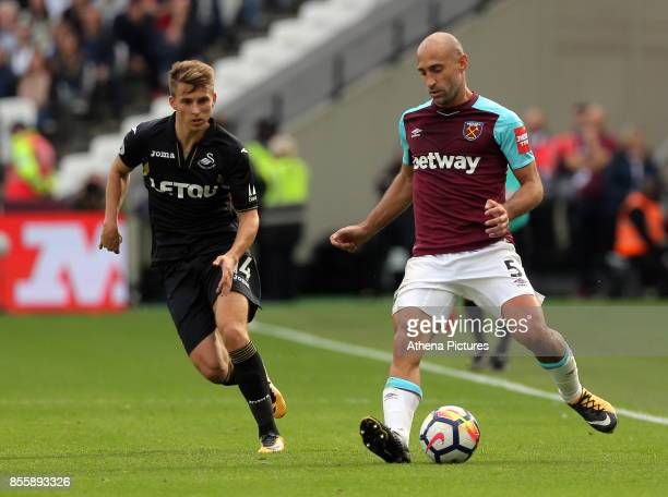 Pablo Zabaleta of West Ham followed by Tom Carroll of Swansea City during the Premier League match between West Ham United v Swansea City at the...
