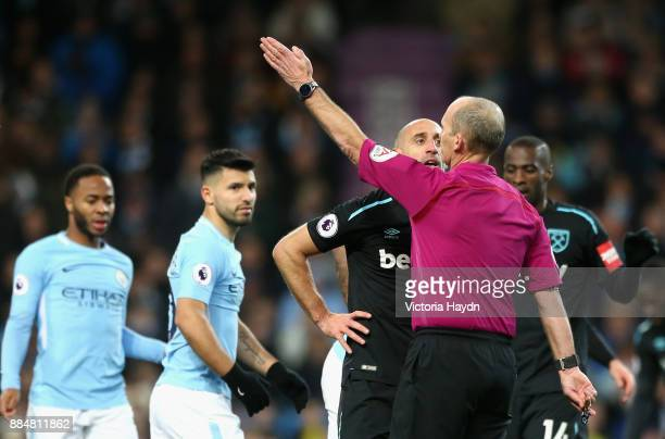 Pablo Zabaleta of West Ham United speaks to referee Mike Dean during the Premier League match between Manchester City and West Ham United at Etihad...